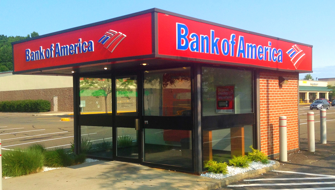 A photograph shows a Bank of America A T M inside a large kiosk in a parking lot