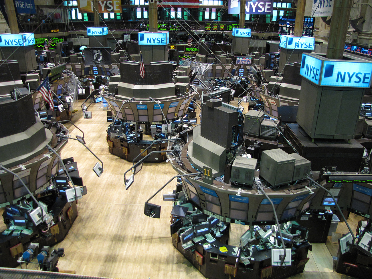 A photograph shows the New York Stock Exchange. The indoor area has many terminals, each one is covered with computers and display screens. In the background there are screens that show stocks and prices.