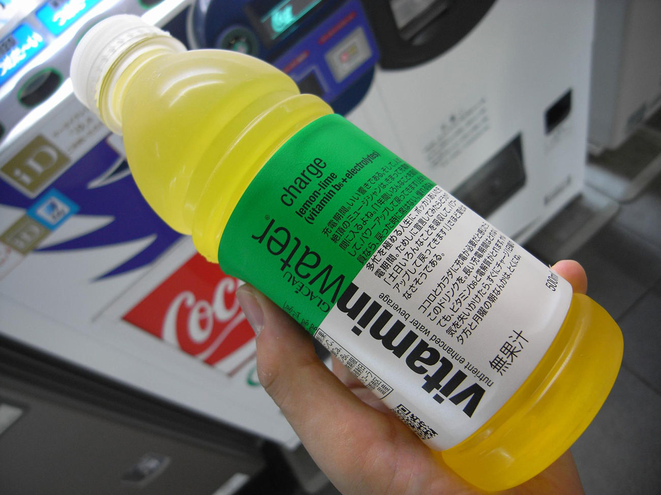 A photograph shows a person holding a bottle of Vitamin water. The label is written in both English and Japanese lettering.