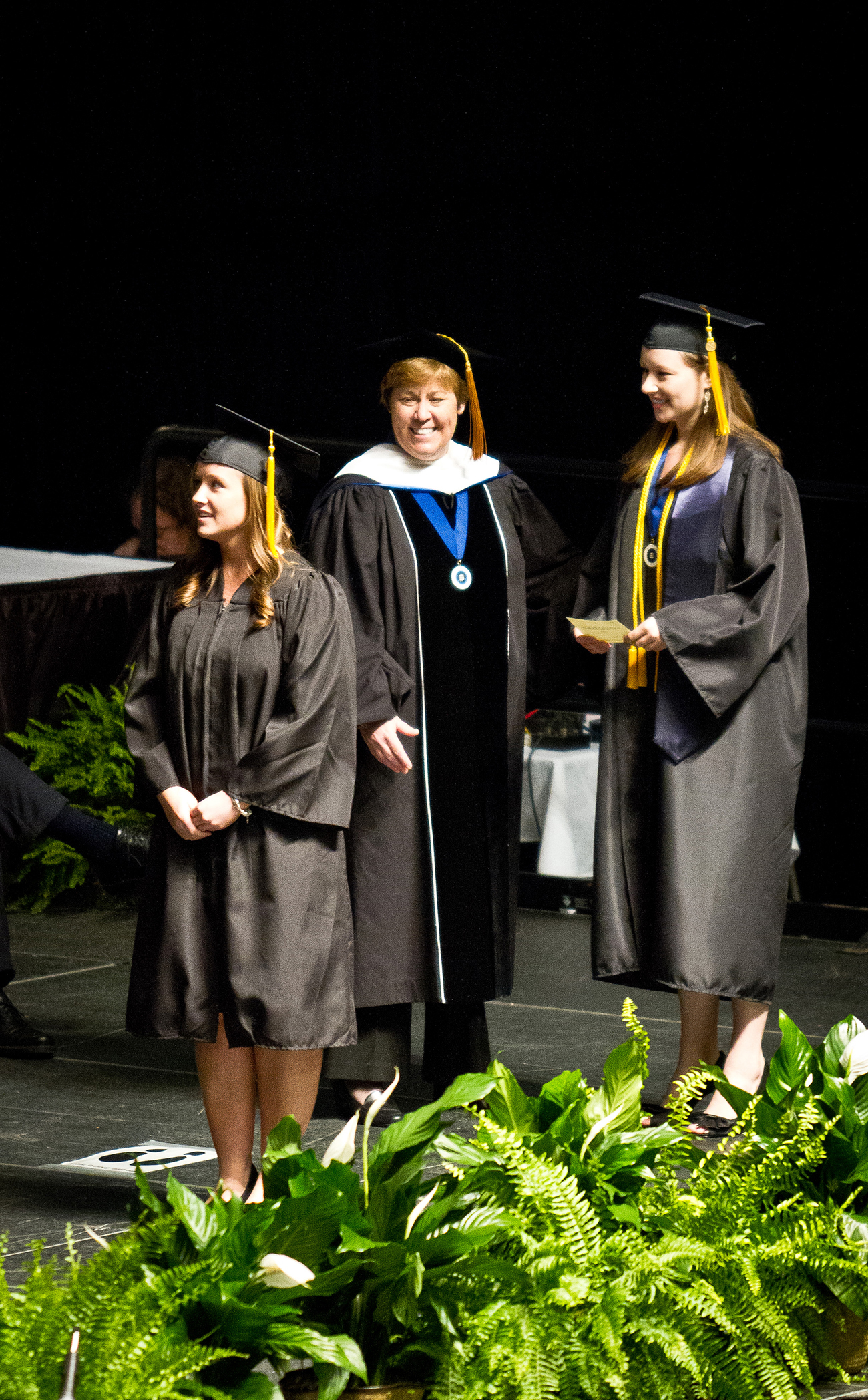 Graduates, wearing cap and gown, walk across a stage to receive their diplomas.