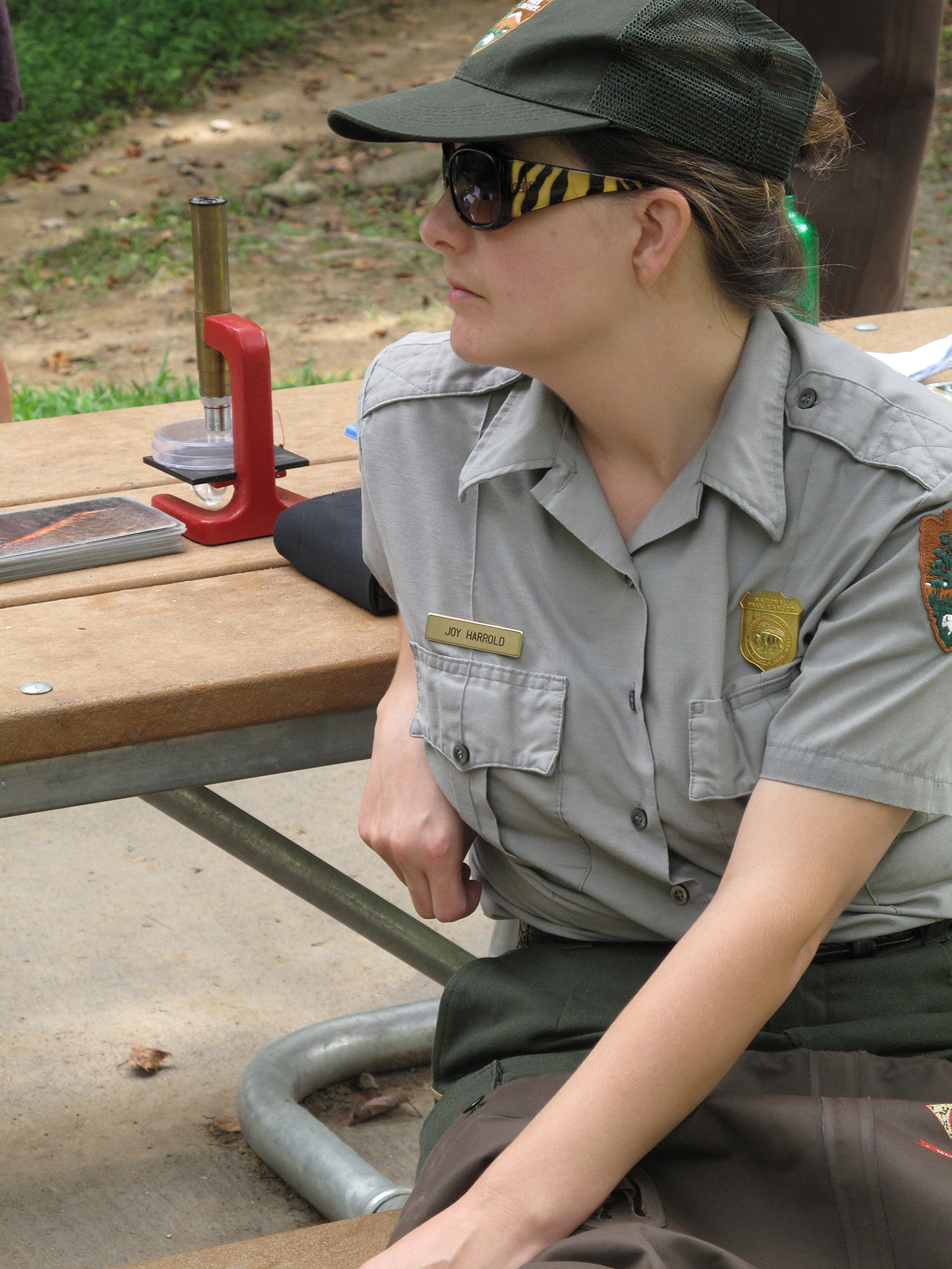 A park ranger, wearing an official uniform and badge, sits at a picnic table outside.