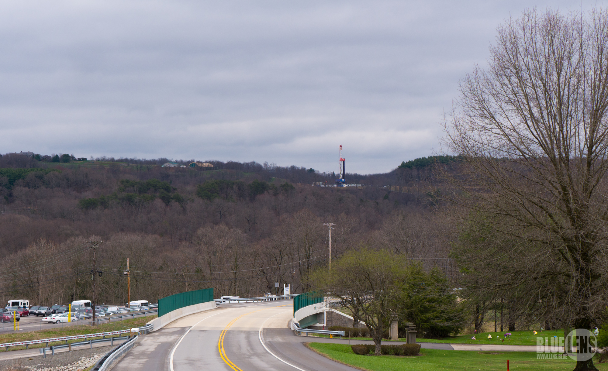 A photograph shows a rural landscape, and on the hill in the distance is a large, high tech drill.