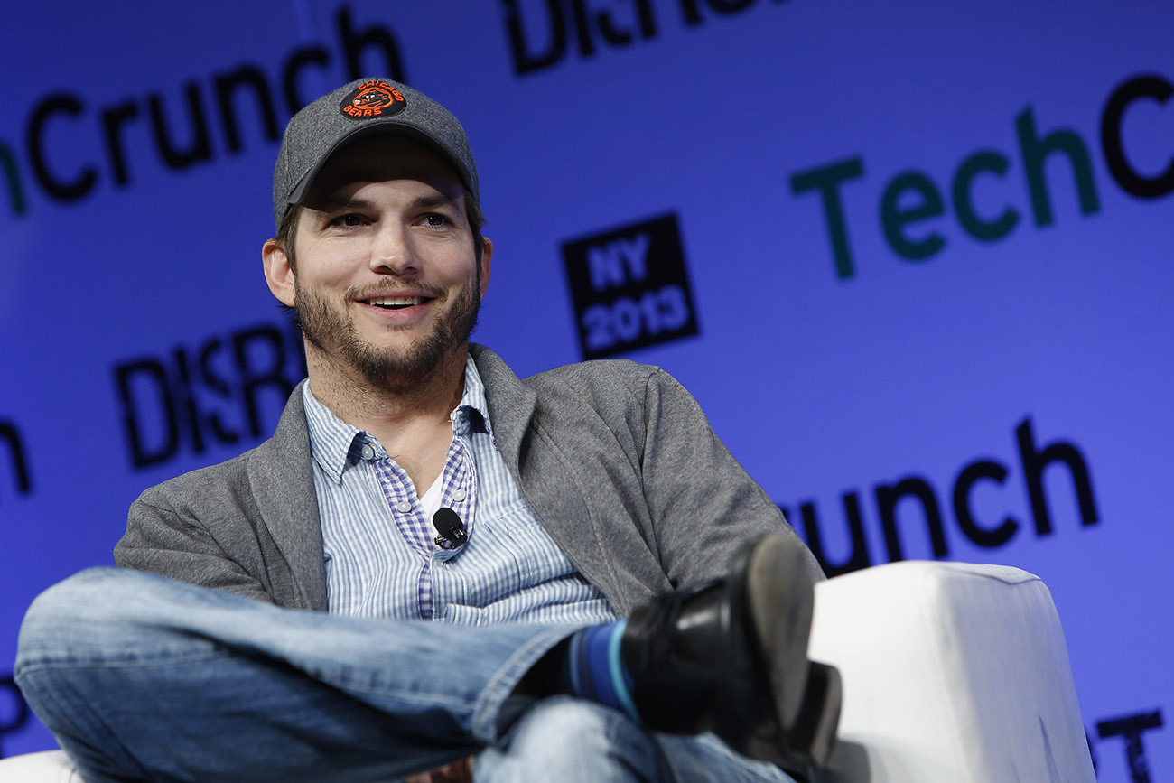 A photograph shows Ashton Kutcher sitting in front of a digital screen that reads Tech Crunch, N Y 2013.
