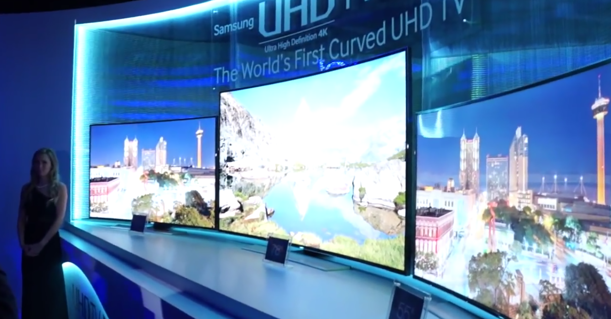 A photograph shows a large television with a concave screen. Above the television display is a sign that reads, Samsung U H D, the world's first curved U H D T V.