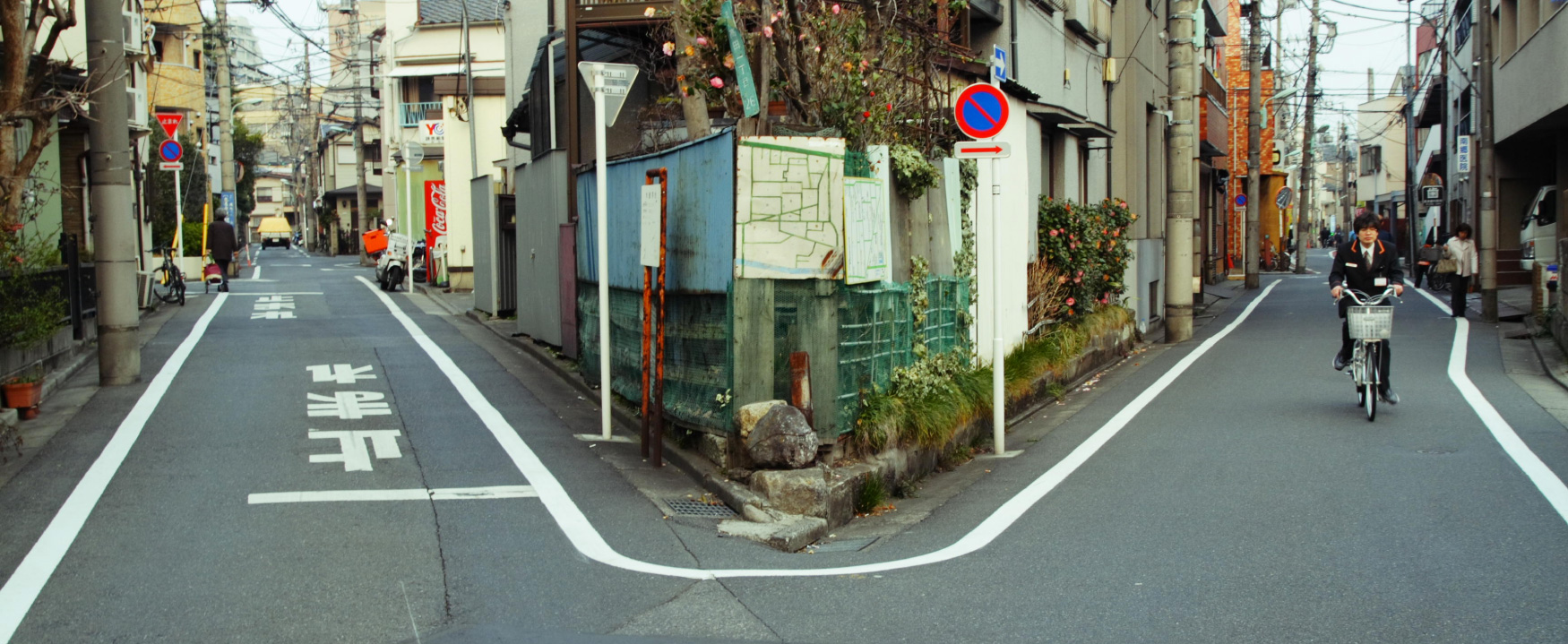 A photograph shows a street that branches into 2 paths; one going left, and one going right.
