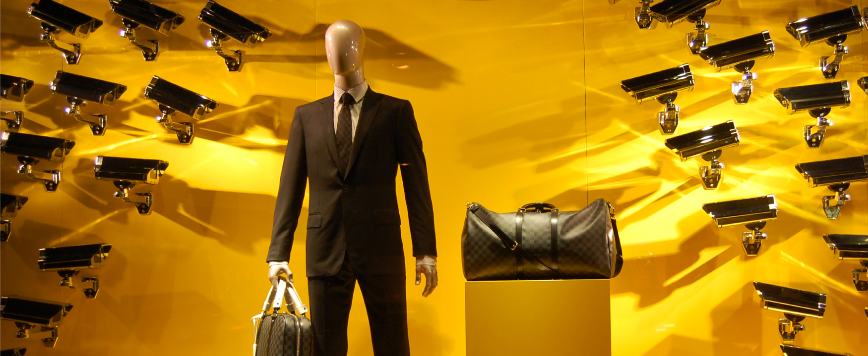 A display shows a mannequin dressed in a business suit, holding a designer bag, with a second designer bag on a pedestal beside it. On the wall behind the mannequin are dozens of security cameras pointed at it, and the bags.