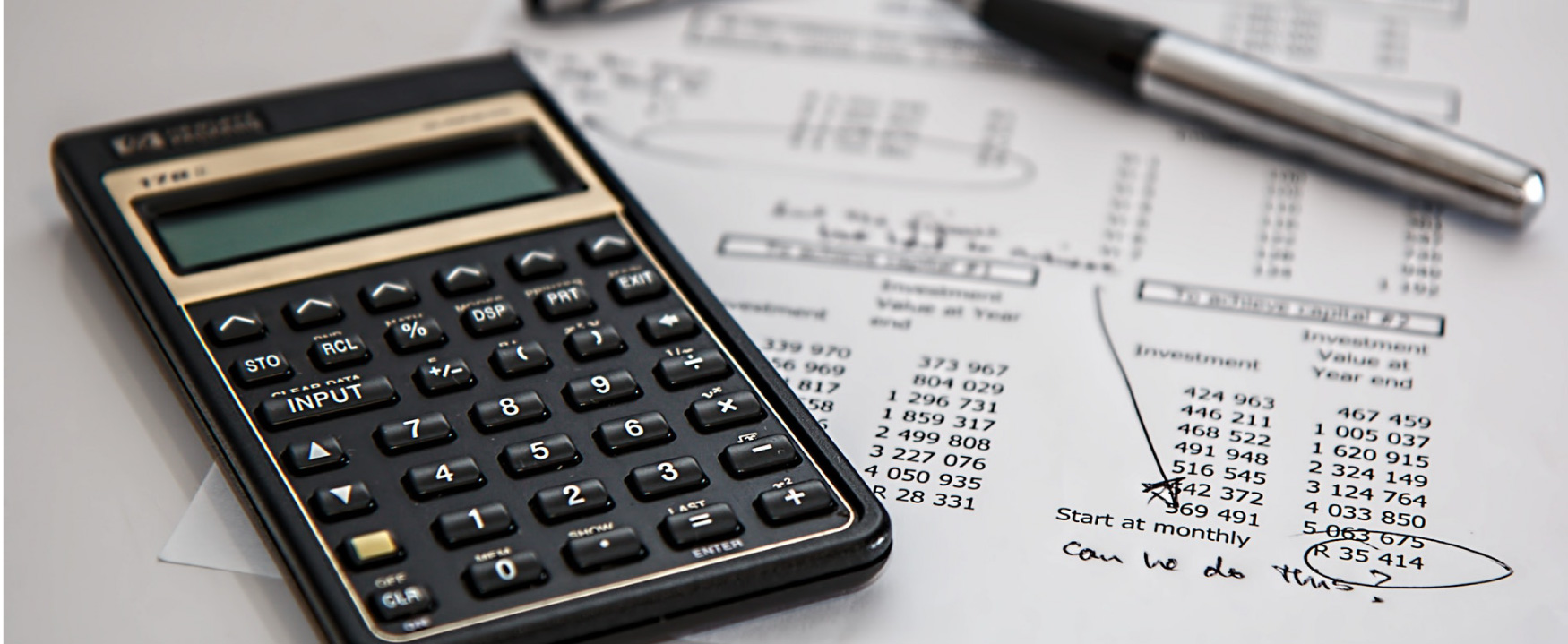 """A calculator sits on a sheet of paper.  On the paper are investment and return amounts, with a handwritten note that asks, """"Can we do this?"""""""