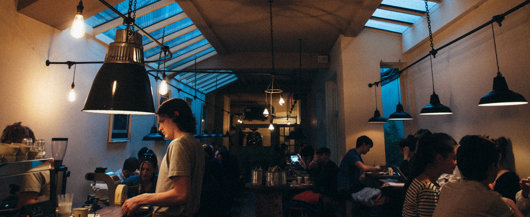 A dimly lit, crowded coffee shop is shown.  Patrons sit at tables, and a worker attends to a customer at the counter.