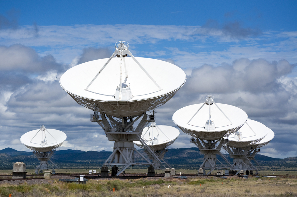 This image is a picture of radio telescopes. They have large parabolic domes as the receivers with an antenna in the center.
