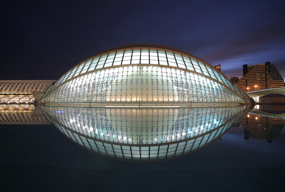 A photo of a glass ovoid dome reflecting in the water to make something like a football shape.