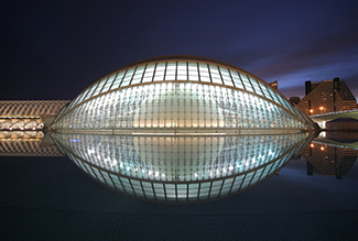 A picture of l'Hemisphèric, which is a giant glass structure that is in the shape of an ellipsoid.