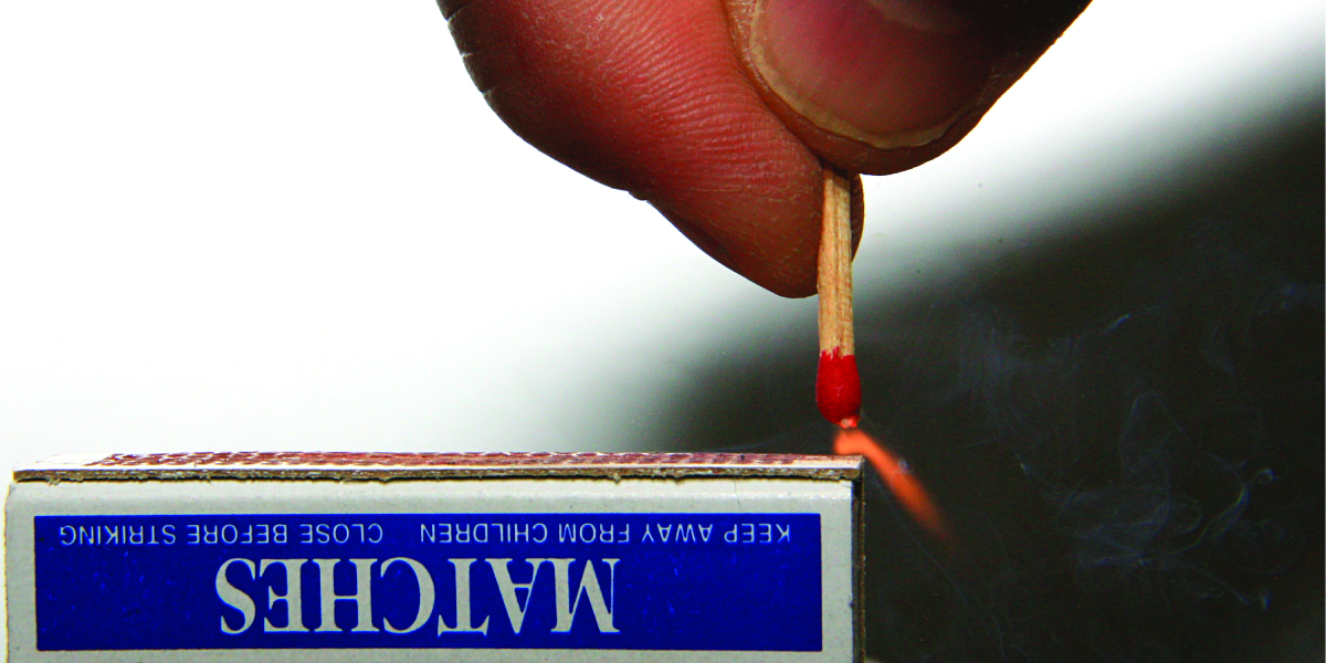 A match held in a person's hand is ignited as it is scratched along the rough surface of a match box.