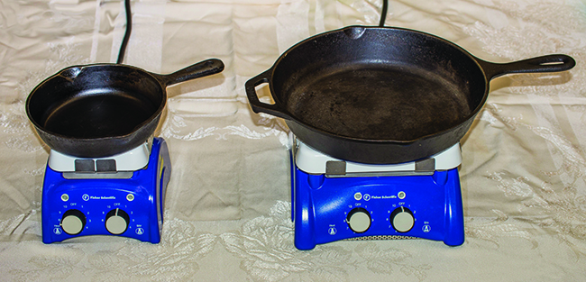 The picture shows two black metal frying pans sitting on a flat surface. The left pan is about half the size of the right pan.