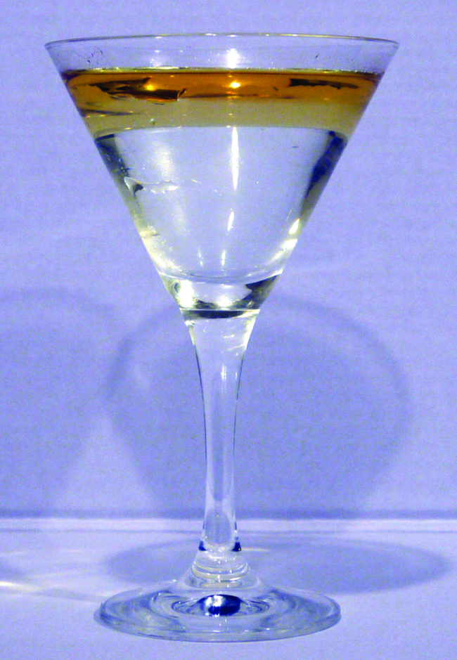 This is a photo of a clear, colorless martini glass containing a golden colored liquid layer resting on top of a clear, colorless liquid.