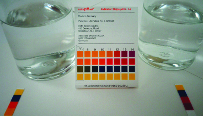 This photo shows two glass containers filled with a transparent liquid. In between the containers is a p H strip indicator guide. There are p H strips placed in front of each glass container. The liquid in the container on the left appears to have a p H of 10 or 11. The liquid in the container on the right appears to have a p H of about 13 or 14.
