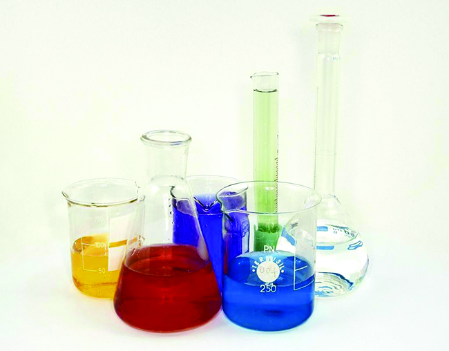 A photo of beakers, flasks, and graduated cylinders is shown. Each piece of glassware holds a different color liquid.
