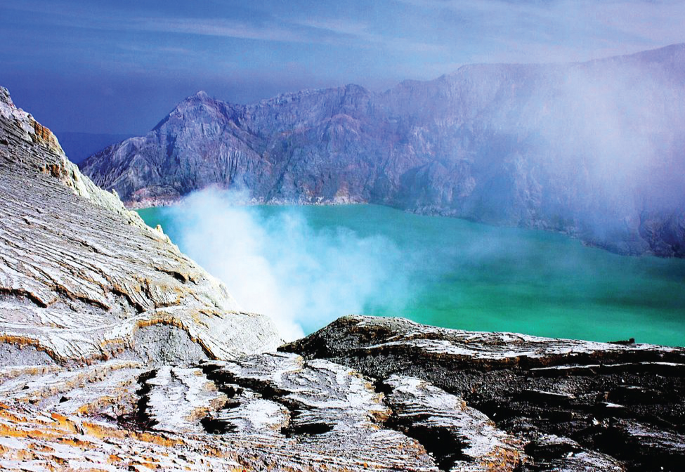 A lake is shown surrounded by rocky, mountainous peaks. A white vapor rises from the ground near the lake.