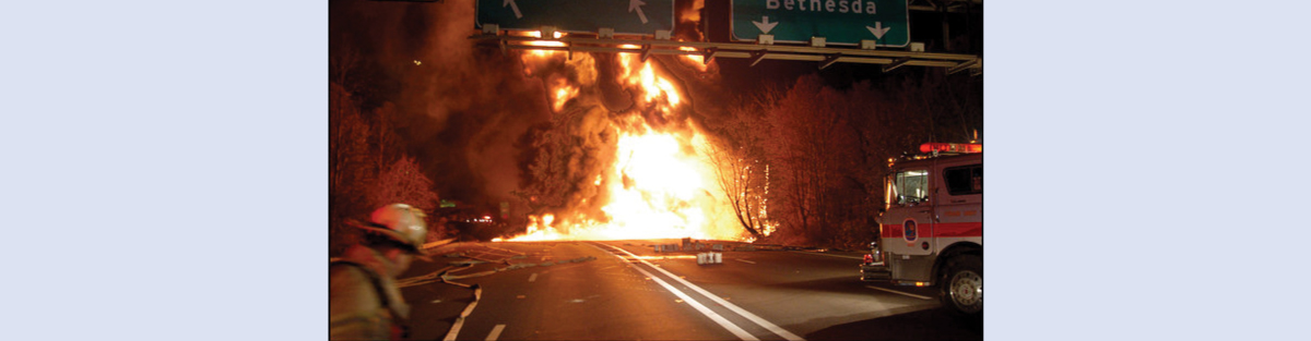 A picture shows a large ball of fire burning on a road. A fire truck and fireman are shown in the foreground.