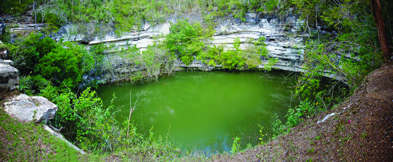 A photograph is shown of a pond formed in a sinkhole. Layers of limestone with trees and shrubs surround the murky green water of the pond.
