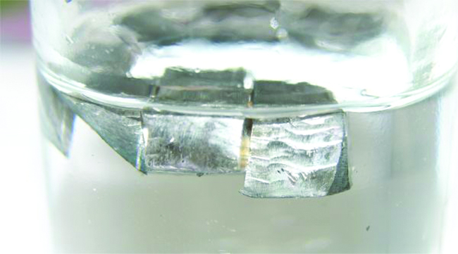 A glass container that is half filled with a colorless liquid is shown. Blocks of a shiny silver solid float on top of the liquid in the container.