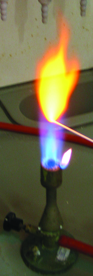 A photo of a lit Bunsen burner is shown. A wooden splint is placed in the flame, and a yellow flame is produced.