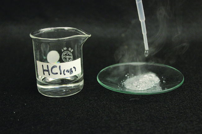 """A photo shows a beaker that contains a clear, colorless liquid. It is labeled, """"H C l ( a q )."""" Beside the beaker is a watch glass with a dropper above it. The dropper is releasing liquid into a fizzing liquid. The fizzing liquid is releasing a white gas."""