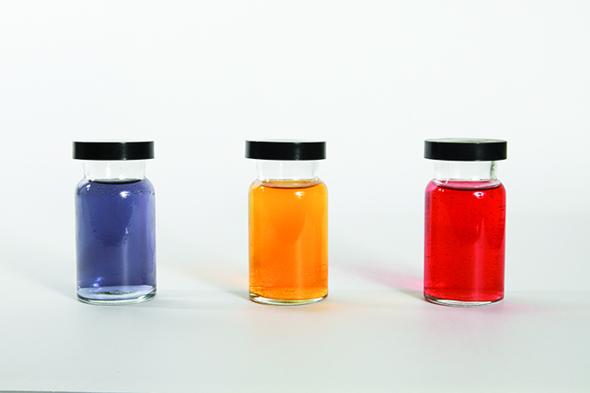 This figure shows three containers filled with liquids of different colors. The first appears to be purple, the second, orange, and the third red.