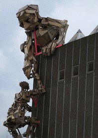 A sculpture of a person helping someone climb a building