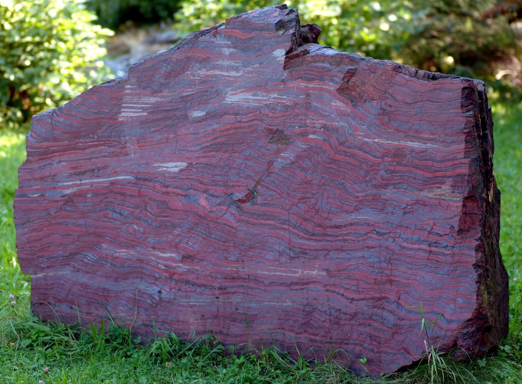 Figure 20.7 Banded iron formation from an unknown location in North America on display at a museum in Germany. The rock is about 2 m across. The dark grey layers are magnetite and the red layers are hematite. Chert is also present. [https://upload.wikimedia.org/wikipedia/commons/5/5f/Black-band_ironstone_%28aka%29.jpg]