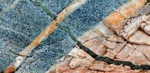 Figura 3.1 Un dique máfica de grano fino (verde oscuro) se introdujo en un dique félsico (rosa) y en diorita gruesa (gris), Quadra Island, BC Todas estas rocas se componen de más de un tipo de mineral. Los componentes minerales son claramente visibles en la diorita, pero no en los otros dos tipos de roca. [Foto SE]