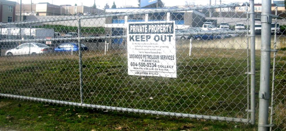 Figure 14.23 A closed and fenced gas station site in Nanaimo, B.C. The white pipes in the background are wells for monitoring groundwater contamination on the site. [SE]