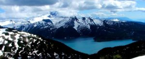 Figure 4.2 Mt. Garibaldi (background left, looking from the north) with Garibaldi Lake in the foreground. The volcanic peak in the centre is Mt. Price and the dark flat–topped peak is The Table. All three of these volcanoes were active during the last glaciation. [SE photo]