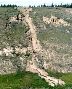 Figure 15.16 A slump (left) and an associated mudflow (centre) at the same location as Figure 15.15, near Lethbridge, Alberta. [SE]