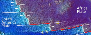 Figure 10.15 A part of the mid-Atlantic ridge near the equator. The double white lines are spreading ridges. The solid white lines are fracture zones. As shown by the yellow arrows, the relative motion of the plates on either side of the fracture zones can be similar (arrows pointing the same direction) or opposite (arrows pointing opposite directions). Transform faults (red lines) are in between the ridge segments, where the yellow arrows point in opposite directions. [SE]