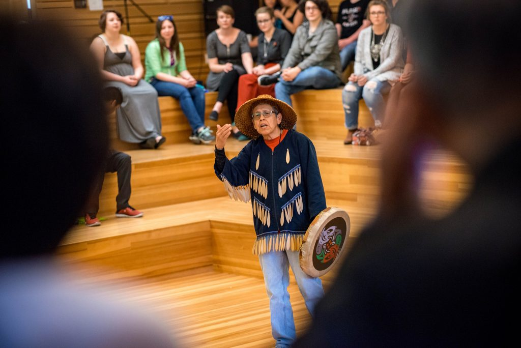 An indigenous man speaks to a crowd at an Indigenous Graduate reception.