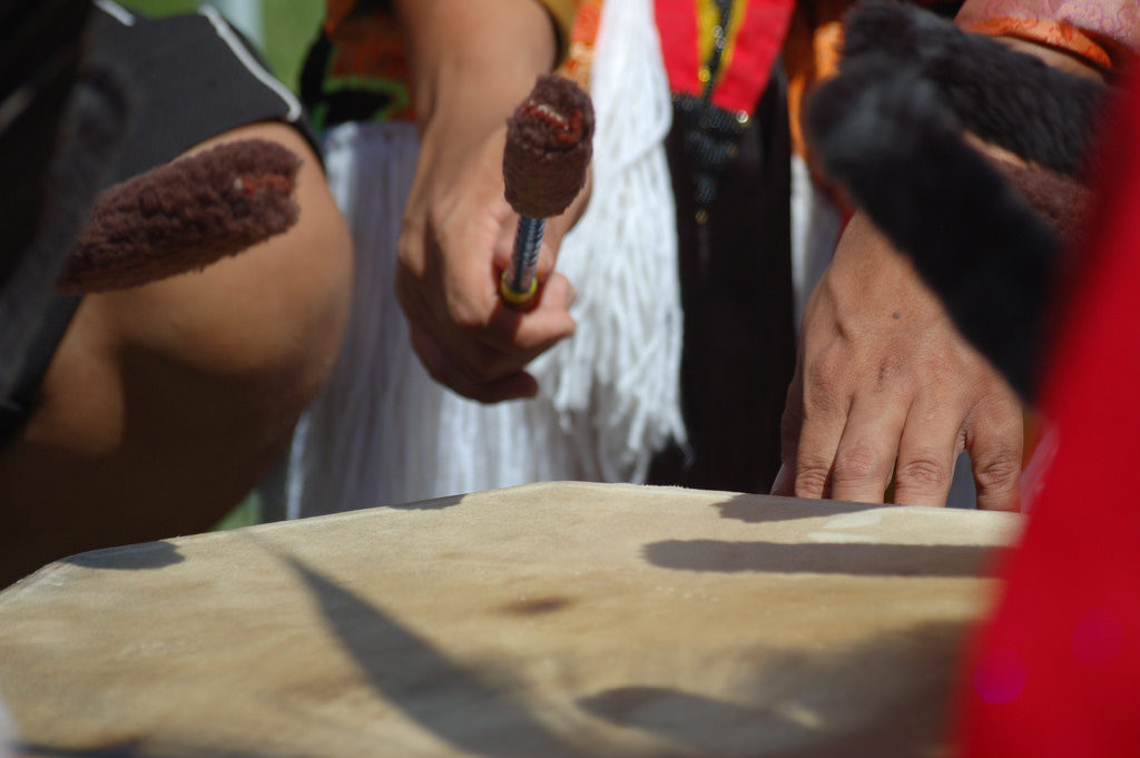 Pow Wow drumming only hands and drum sticks visible