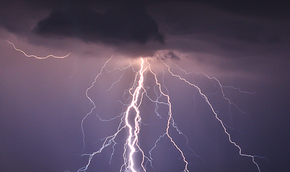 This photo shows branch lightening coming from a dark cloud and hitting the ground.