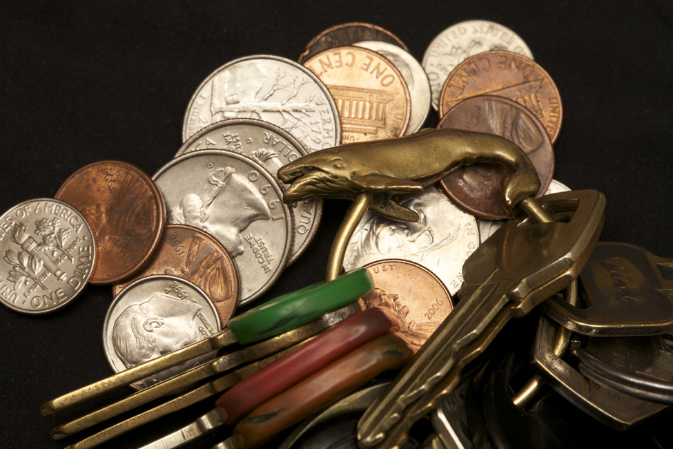 This is a photo of change a set of keys in a pile. There appear to be five pennies, three quarters, four dimes, and two nickels. The key ring has a bronze whale on it and holds eleven keys.
