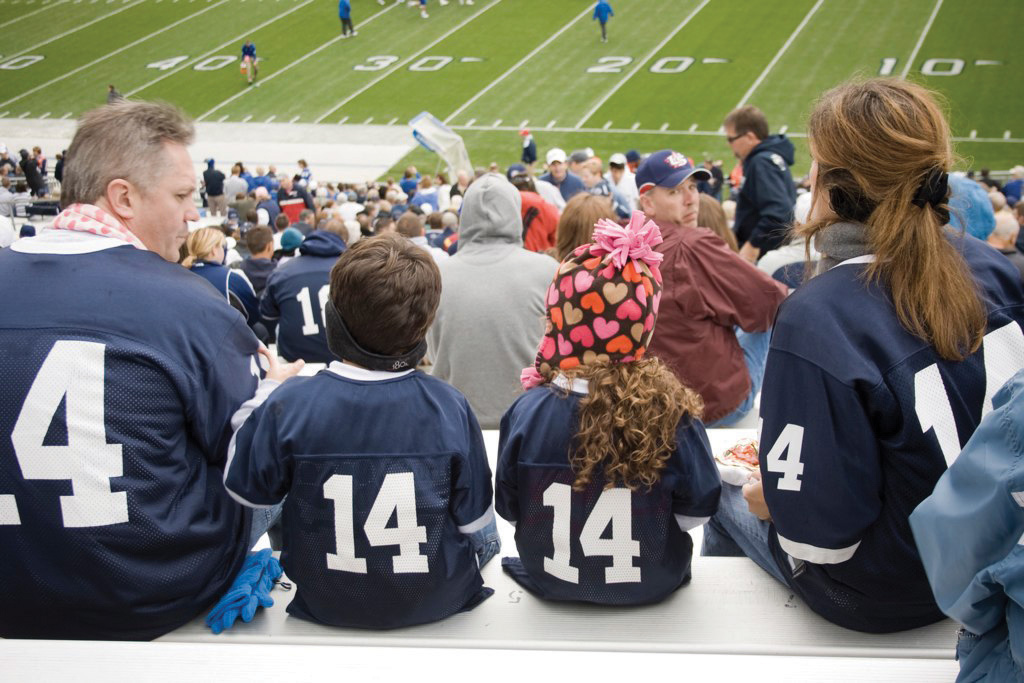 A family wearing matching jerseys at a football game.