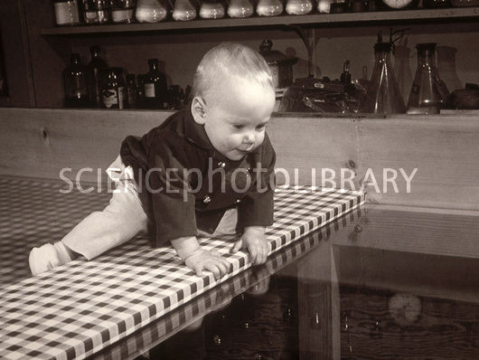 A baby on the edge of a table.
