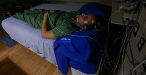 A person sleeps with sensors placed on his face.