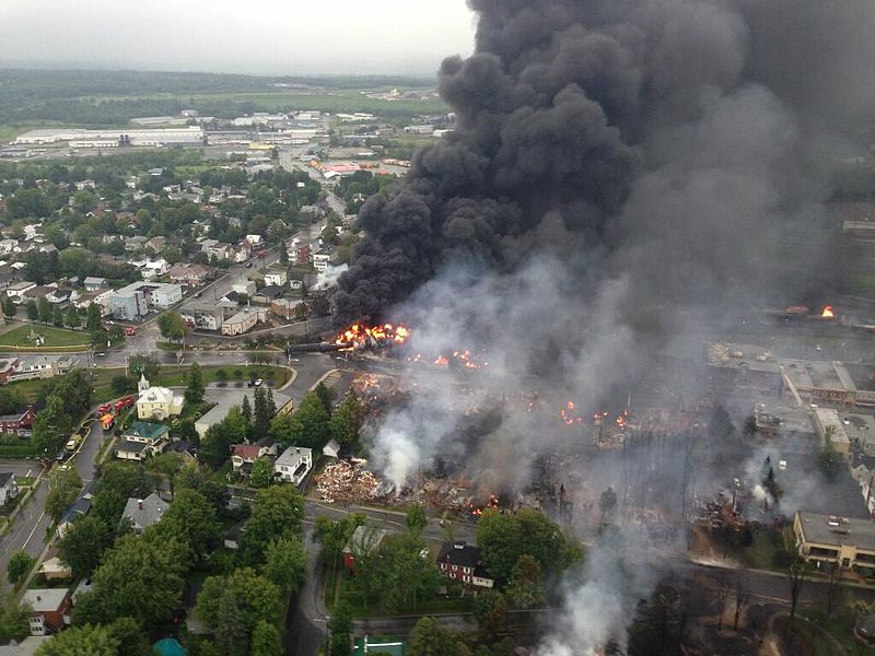 Bird's eye view of black smoke and a town on fire.