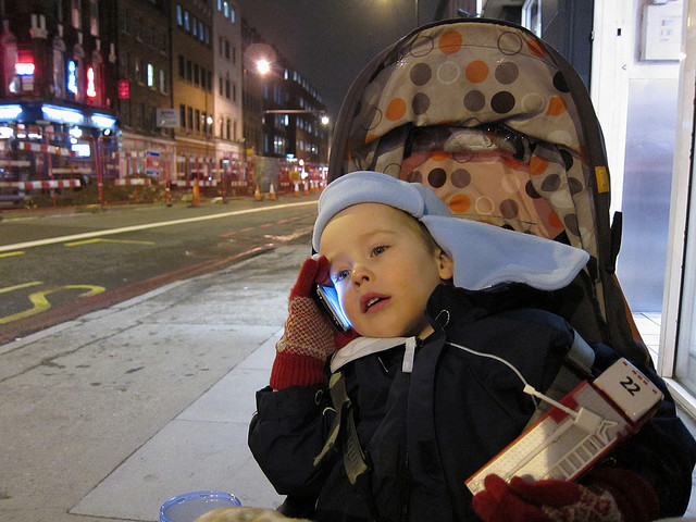 A young child talking on the phone.