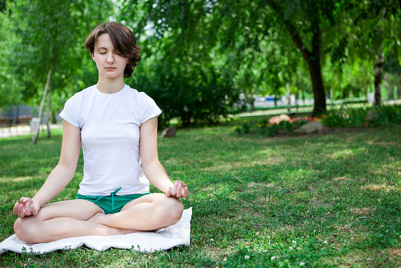 A woman meditates in a park.