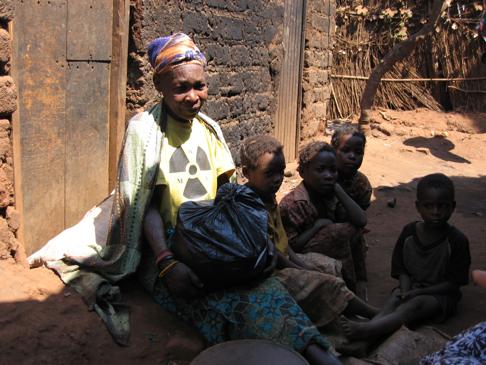 Older African woman sitting on the ground by a rough, brick building and a black plastic bag in her lap, surrounded by four young children.