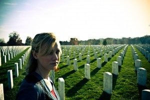 A girl taking an unsmiling selfie in front of a field of tombstones.