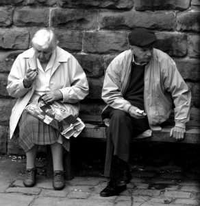 Two older people sitting on a street bench not looking at each other.