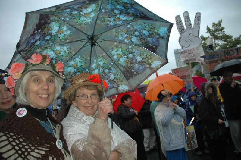 Older women holding umbrellas at a rally.