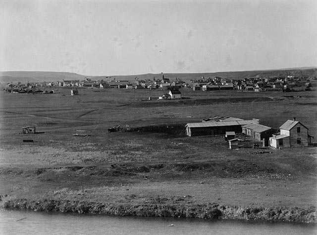 A black and white photo of a small town spread out over a flat plain.