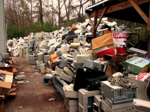 Piles of e-waste including computers and microwaves.